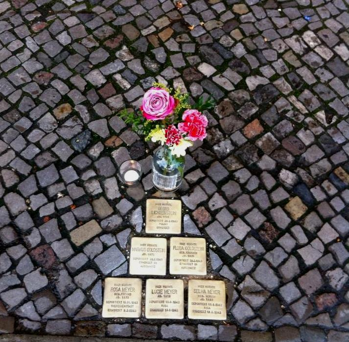 A candle and flowers placed at the Stolpersteine on the anniversary of Kristallnacht