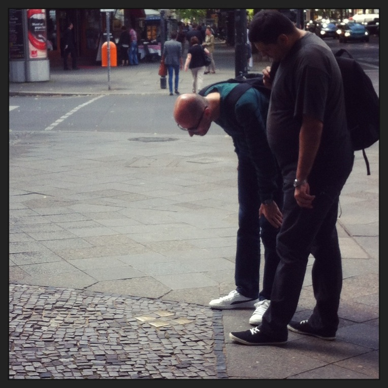 Pedestrians bow to look at Stolpersteine in West Berlin